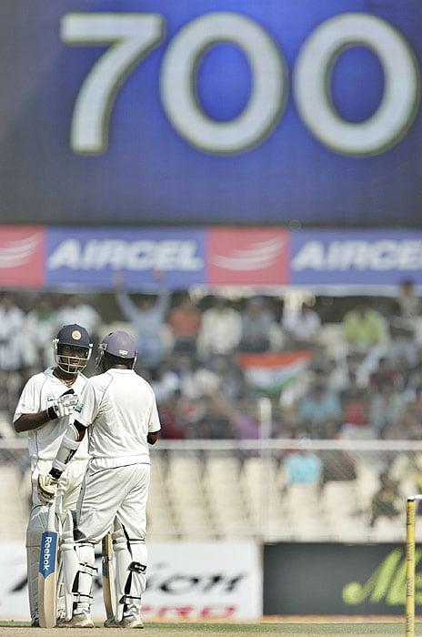 Sri Lanka's Prasanna Jayawardene and Mahela Jayawardene talk as their team score 700 (displayed on the screen) during the fourth day of the first Test against India in Ahmadabad on Thursday. (AP Photo)