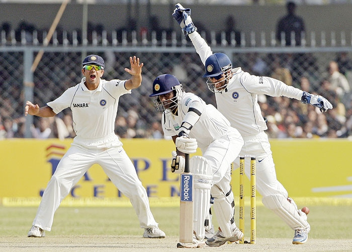 India's captain Mahendra Singh Dhoni and teammate Rahul Dravid celebrate the dismissal of Sri Lanka's Ajantha Mendis during the fourth day of their second Test match in Kanpur on Friday. (AP Photo)