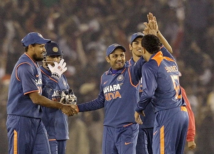 India's Virender Sehwag celebrates with teammates after running out Sri Lanka's Kaushalya Weeraratne during their second Twenty20 match in Mohali on Saturday. (AP Photo)