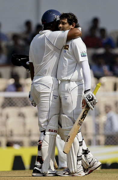 Kumar Sangakkara congratulates teammate Tillakaratne Dilshan for scoring a half-century on the first day of the third Test between India and Sri Lanka in Mumbai. (AP Photo)