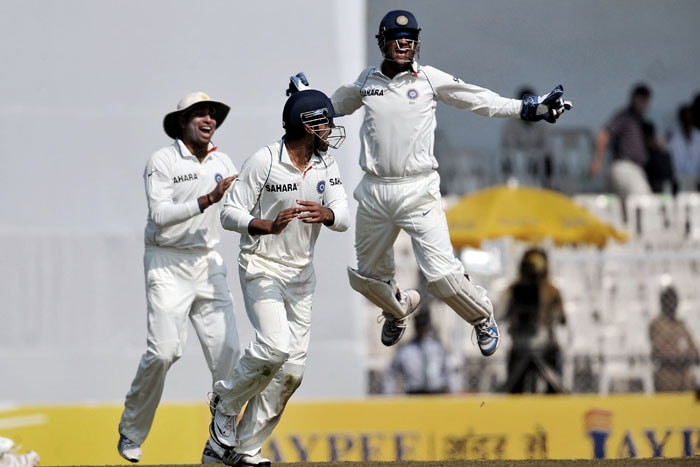 Mahendra Singh Dhoni celebrates the wicket of Kumara Sangakara with teammates on the first day of the third Test between India and Sri Lanka in Mumbai. (AFP Photo)