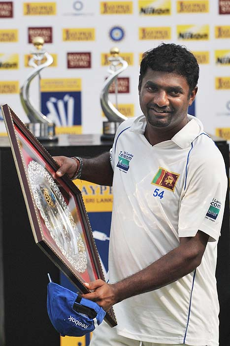 Sri Lanka's Muttiah Muralitharan receives a trophy for his contribution as the Test series' highest wicket-taker on the final day of the third Test against India in Mumbai on Sunday. (AFP Photo)