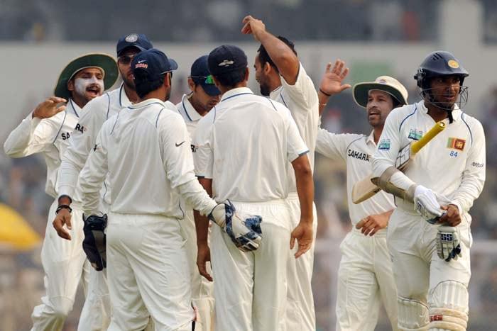Indian cricketers celebrate the wicket of Sri Lanka's Kumara Sangakara on the final day of the third Test in Mumbai on Sunday. (AFP Photo)