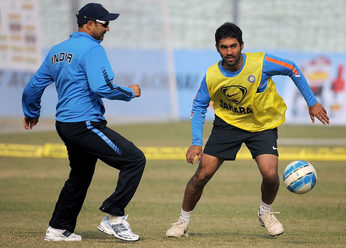 Virender Sehwag and Dinesh Karthik play football during a training session at the Green Park Stadium in Kanpur.