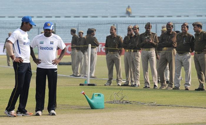 Kumara Sangakkara and Muttiah Muralitharan inspect the pitch duringa training session at the Green Park Stadium in Kanpur.