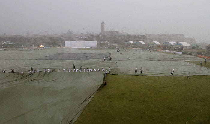 Sri Lankan ground staff cover the cricket ground as it rains during the first day of the first Test between Sri Lanka and India in Galle. (AP Photo)