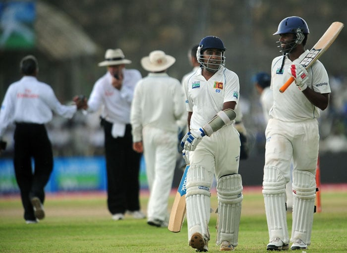 Tharanga Paranavitana and Mahela Jayawardene walk off the field due to rain on the first day of the first Test match between Sri Lanka and India at The Galle International Cricket Stadium in Galle. Sri Lanka were 256 for two at stumps on the opening day. (AFP Photo)