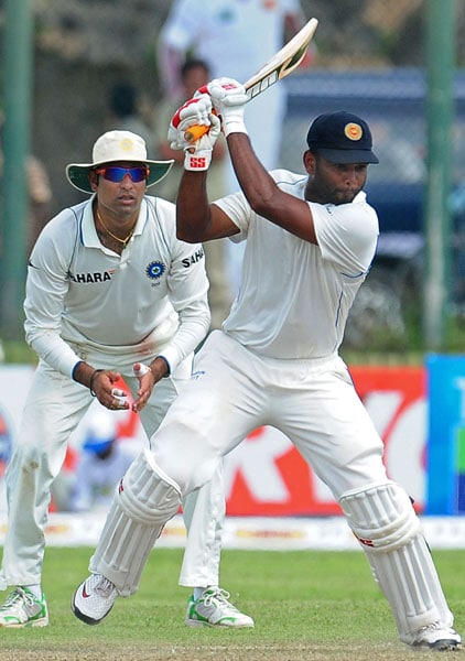 Tharanga Paranavitana plays a stroke while watched by VVS Laxman during the first day of the first Test match between Sri Lanka and India at The Galle International Cricket Stadium in Galle. (AFP Photo)