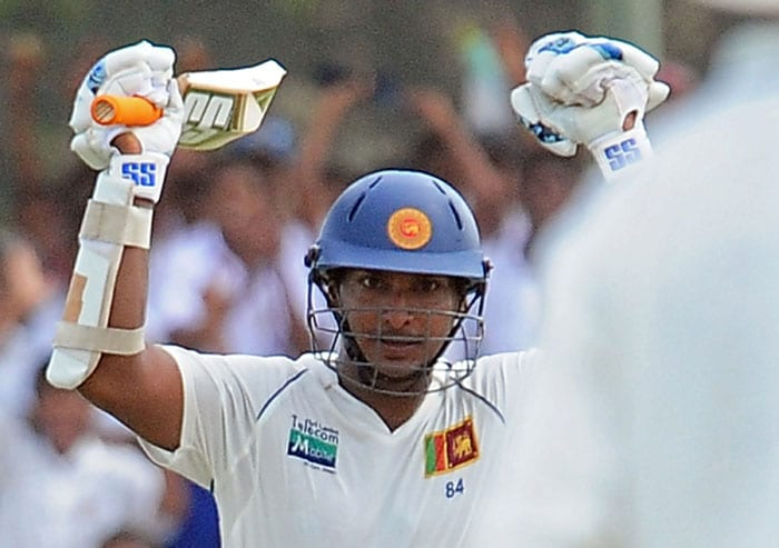 Kumar Sangakkara raises his bat to celebrate scoring a century during the first day of the first Test match between Sri Lanka and India at The Galle International Cricket Stadium in Galle. (AFP Photo)