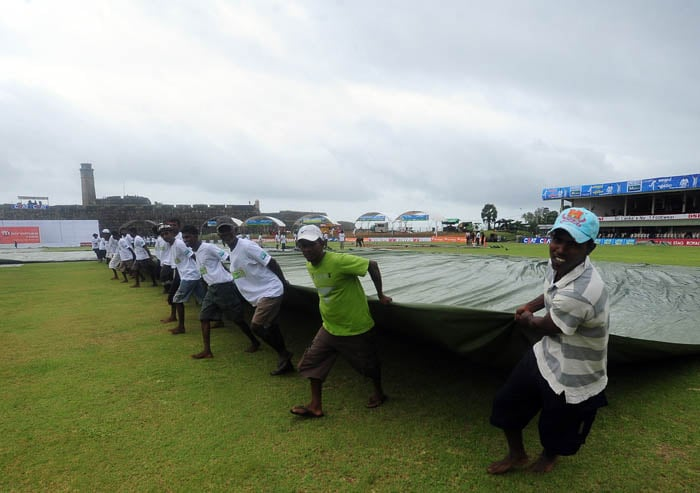 Ground staff pull a tarp to cover the ground as rain delays the start of the second day of the first Test match between Sri Lanka and India in Galle. (AFP Photo)