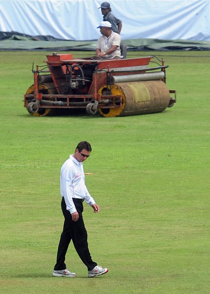 Australian umpire Rodney Tucker inspects the pitch following rain that delayed the start of the second day of the first Test match between Sri Lanka and India in Galle. (AFP Photo)