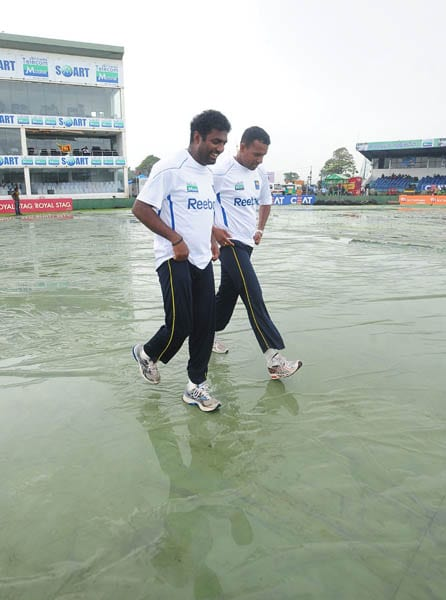 Sri Lankan cricketer Muttiah Muralitharan and Thilan Samaraweera inspect the pitch following rain that delayed the start of the second day of the first Test match between Sri Lanka and India in Galle. (AFP Photo)