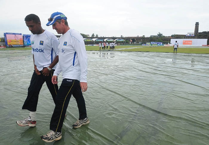 Thilan Samaraweera and coach Trevor Bayliss inspect the pitch following rain that delayed the start of the second day of the first Test match between Sri Lanka and India in Galle. (AFP Photo)