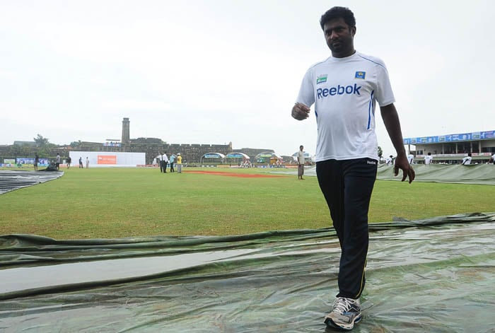 Muttiah Muralitharan inspects the pitch following rain that delayed the start of the second day of the first Test match between Sri Lanka and India in Galle. (AFP Photo)