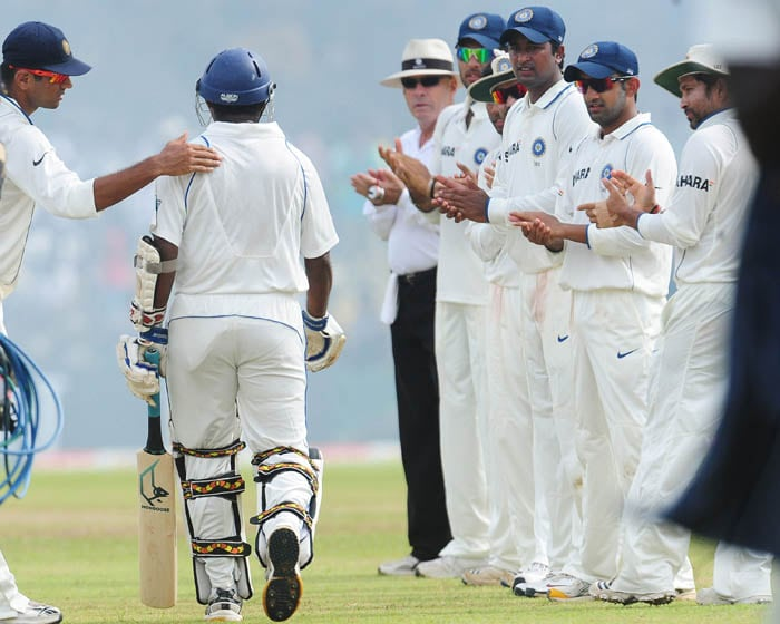 Indian cricketers applaud as Muttiah Muralitharan makes his way to bat in the first innings during the third day of the first Test match between Sri Lanka and India in Galle. (AFP Photo)