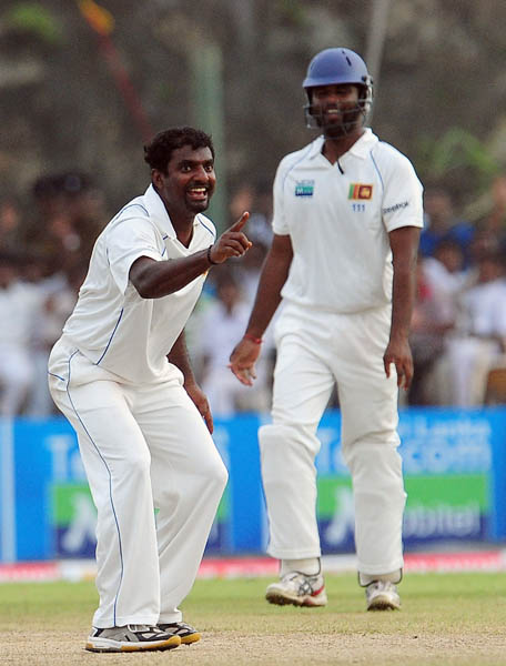 Muttiah Muralitharan celebrates with his teammate Tharanga Paranavitana the dismissal of Sachin Tendulkar during the third day of the first Test match between Sri Lanka and India in Galle. (AFP Photo)