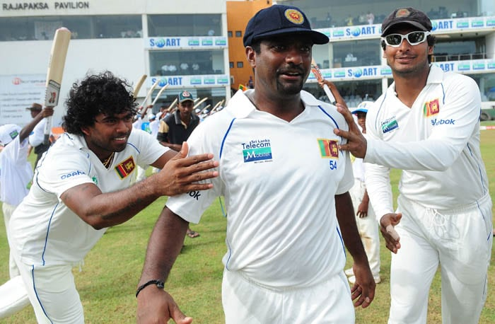 Muttiah Muralitharan is greeted by captain Kumar Sangakkara and Lasith Malinga as he makes his way to the field at the start of India's first innings during the third day of the first Test match between Sri Lanka and India in Galle. (AFP Photo)