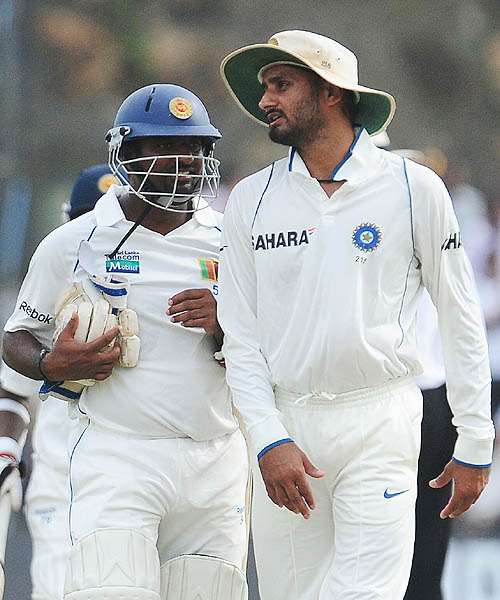 Muttiah Muralitharan chats with Indian bowler Harbhajan Singh after batting in the first innings during the third day of the first Test match between Sri Lanka and India in Galle. (AFP Photo)