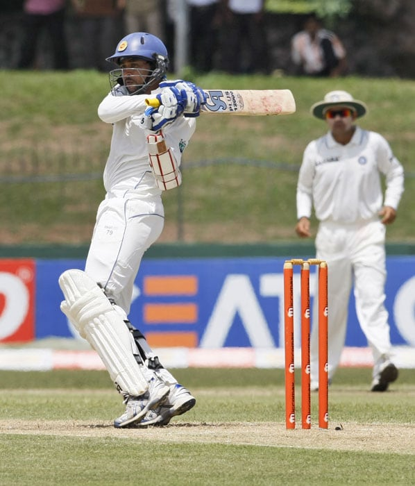 Tillakaratne Dilshan plays a shot as India's Virender Sehwag looks on during the first day's play of the second Test between India and Sri Lanka in Colombo. (AP Photo)