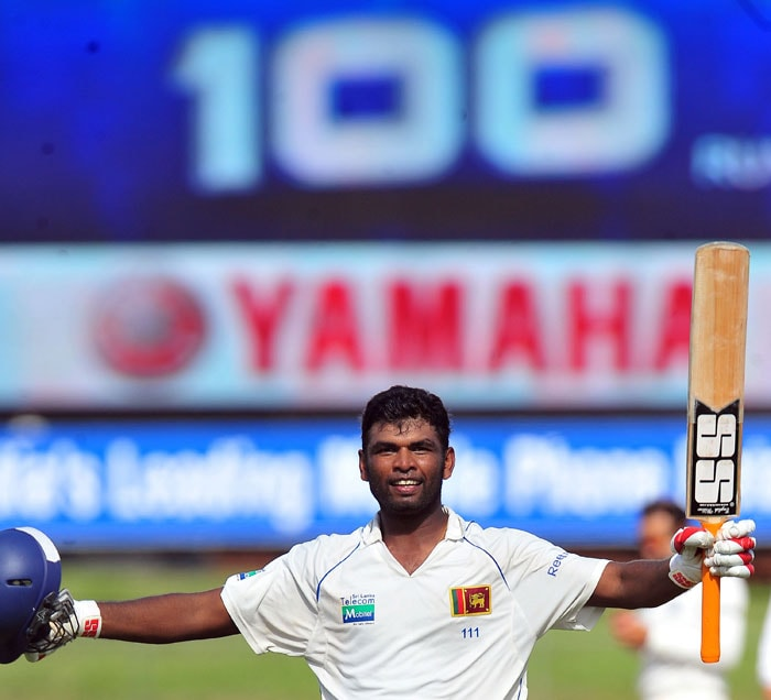Tharanga Paranavitana raises his bat and helmet in celebration after scoring a century (100 runs) during the first day of the second Test match between Sri Lanka and India in Colombo. (AFP Photo)