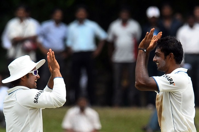 Abhimanyu Mithun celebrates with teammate Suresh Raina the dismissal of Tillakaratne Dilshan during the fifth and final day of the second Test match between Sri Lanka and India in Colombo. (AFP Photo)