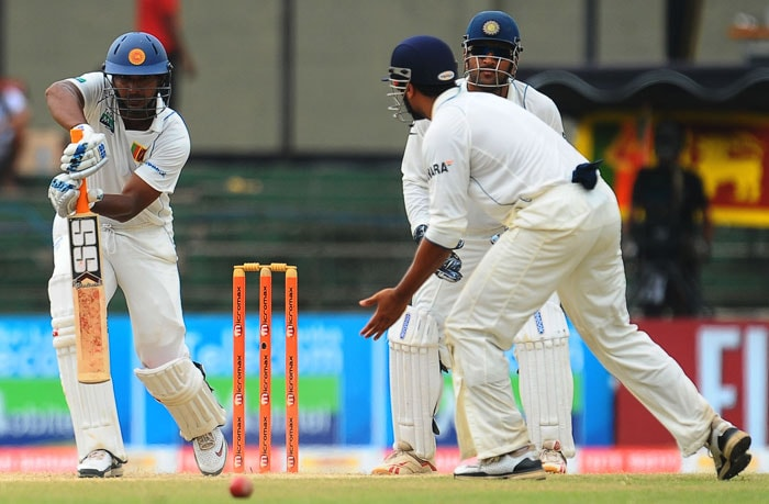 Kumar Sangakkara plays a stroke while watched by Indian captain and wicketkeeper Mahendra Singh Dhoni and bowler Murali Vijay during the fifth and final day of the second Test match between Sri Lanka and India in Colombo. (AFP Photo)