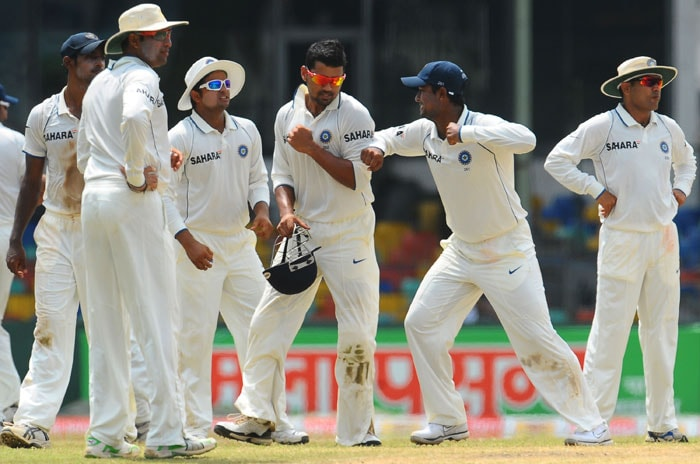 Pragyan Ojha shares a light moment with teammate Murali Vijay during the fifth and final day of the second Test match between Sri Lanka and India in Colombo. (AFP Photo)