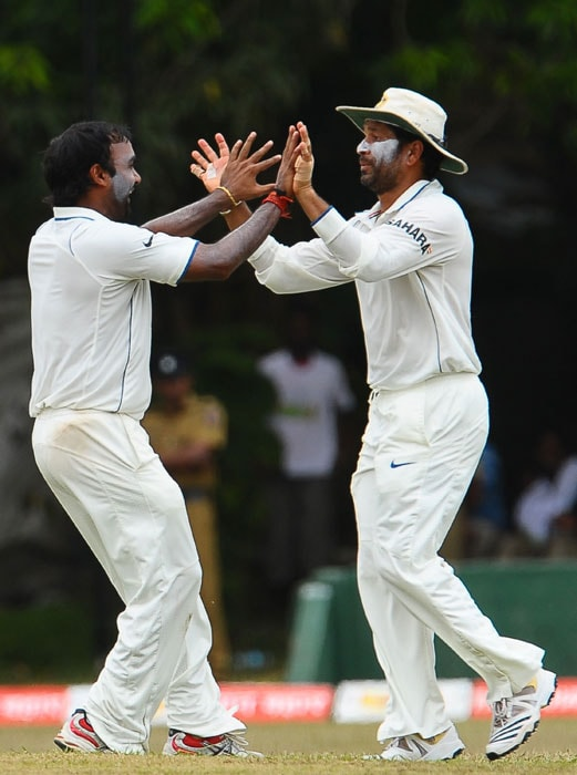Amit Mishra celebrates with his teammate Sachin Tendulkar after the dismissal of unseen Sri Lankan cricketer Anjelo Mathews during the fourth day of the third Test match between Sri Lanka and India in Colombo. (AFP Photo)