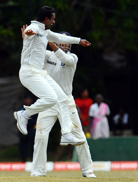 Pragyan Ojha celebrates with his teammates Murali Vijay after the dismissal of Kumar Sangakkara during the fourth day of the third Test match between Sri Lanka and India in Colombo. (AFP Photo)