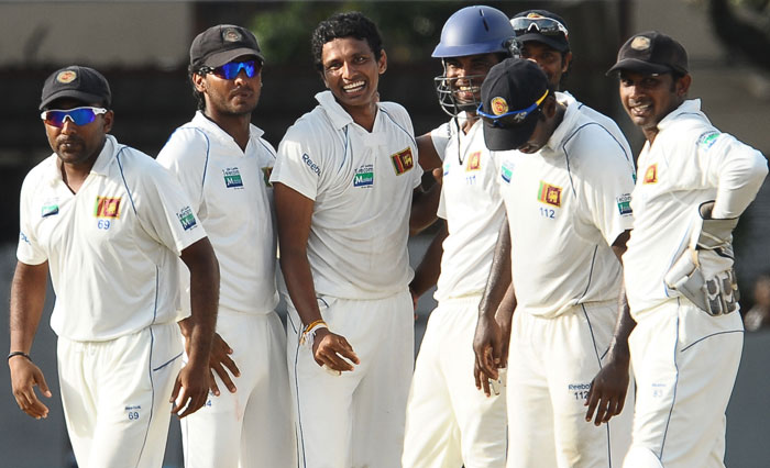 Suraj Randiv celebrates with teammates after the dismissal of Rahul Dravid during the fourth day of the third Test match between Sri Lanka and India in Colombo. (AFP Photo)