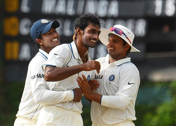 Abhimanyu Mithun celebrates with teammates Pragyan Ojha and Suresh Raina after the dismissal of Thilan Samaraweera during the fourth day of the third Test match between Sri Lanka and India in Colombo. (AFP Photo)