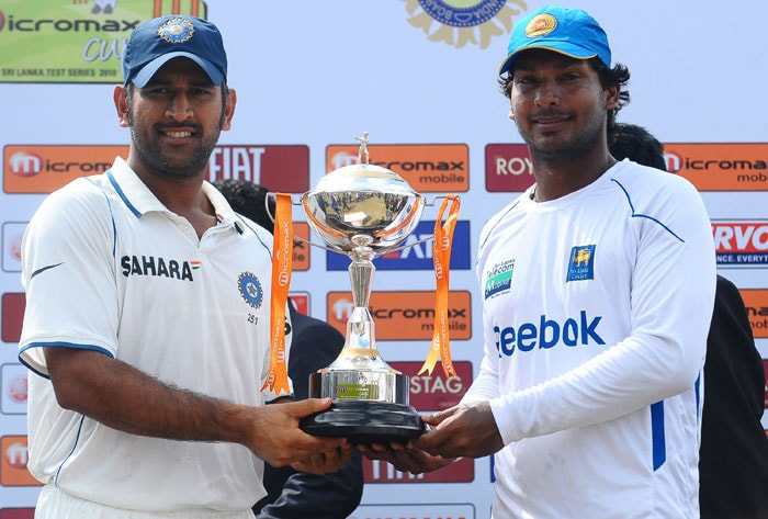 Indian captain Mahendra Singh Dhoni and Sri Lankan captain Kumar Sangakkara hold the trophy following their third Test match between Sri Lanka and India in Colombo. (AFP Photo)