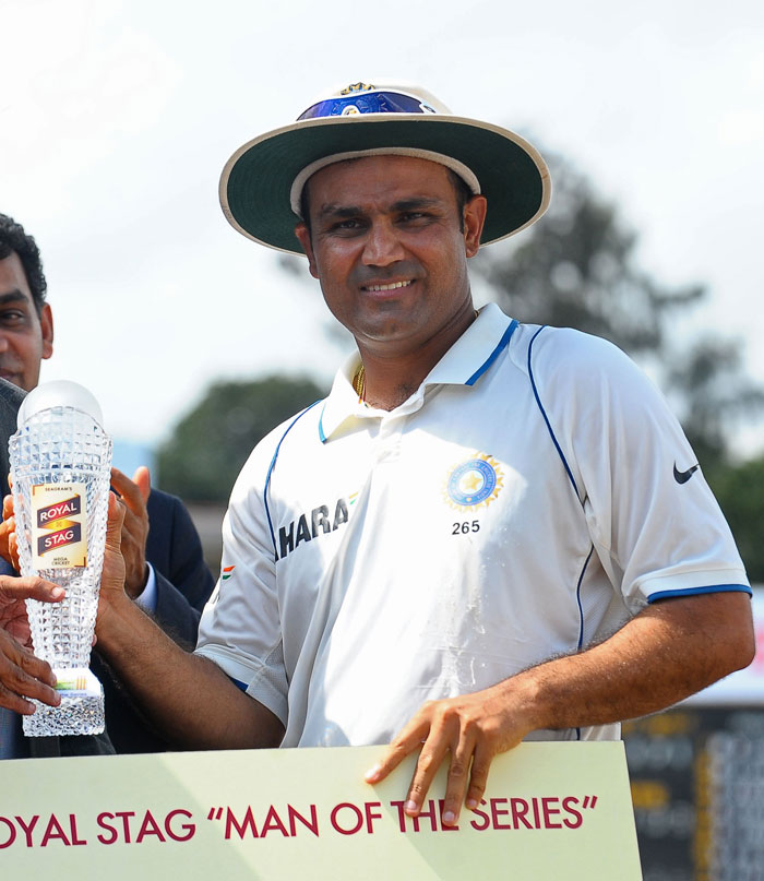 Virender Sehwag poses with the Man of The Series trophy following the third Test match between Sri Lanka and India in Colombo. (AFP Photo)