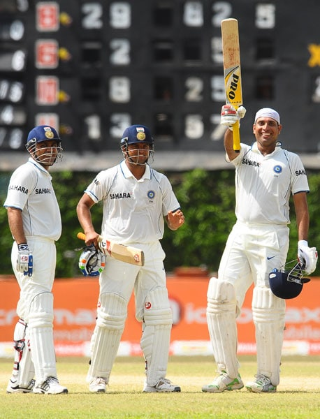 VVS Laxman raises his bat in celebration after scoring a century as teammates Suresh Raina and Virender Sehwag look on during the fifth and final day of the third Test match between Sri Lanka and India in Colombo. (AFP Photo)