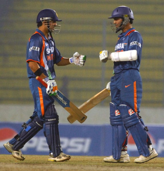 Gautam Gambhir and Dinesh Karthik celebrate after hitting a four during the fifth ODI of the tri-series in Dhaka. (AFP Photo)