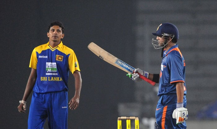Gautam Gambhir acknowledges the crowd after scoring a half-century (fifty runs) as Chanaka Welegedara looks on during the fifth ODI of the tri-series in Dhaka. (AFP Photo)