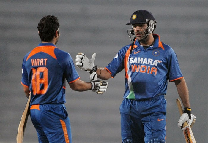 Indian cricketers Virat Kohli and Yuvraj Singh congratulate each other for their team's win during the fifth ODI of the tri-series in Dhaka. (AFP Photo)