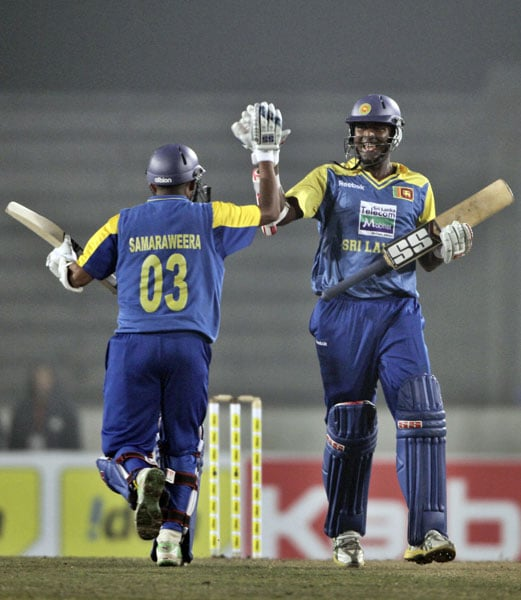 Thissara Perera and Thilan Samaraweera celebrate as they run to complete the winning run against India during the second ODI of the tri-nation tournament in Dhaka. (AP Photo)