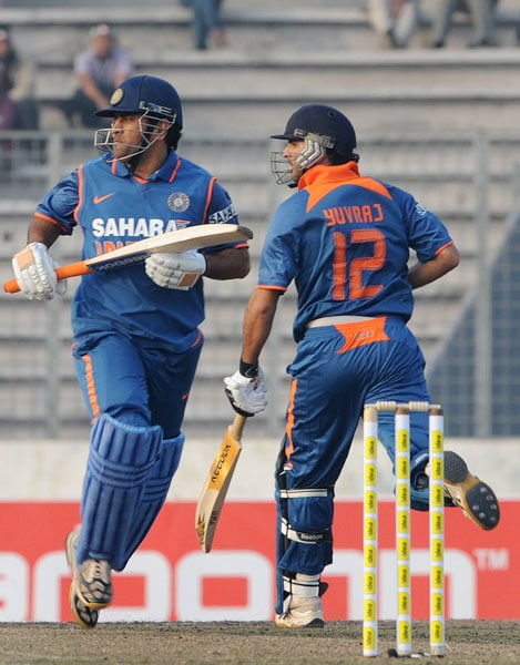 Indian captain Mahendra Singh Dhoni and teammate Yuvraj Singh take a quick single during the second ODI of the tri-nation tournament in Dhaka. (AFP Photo)