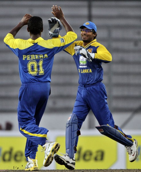 Kumar Sangakkara and Thissara Perera celebrate the dismissal of Yuvraj Singh during the second ODI of the tri-nation tournament in Dhaka. (AP Photo)