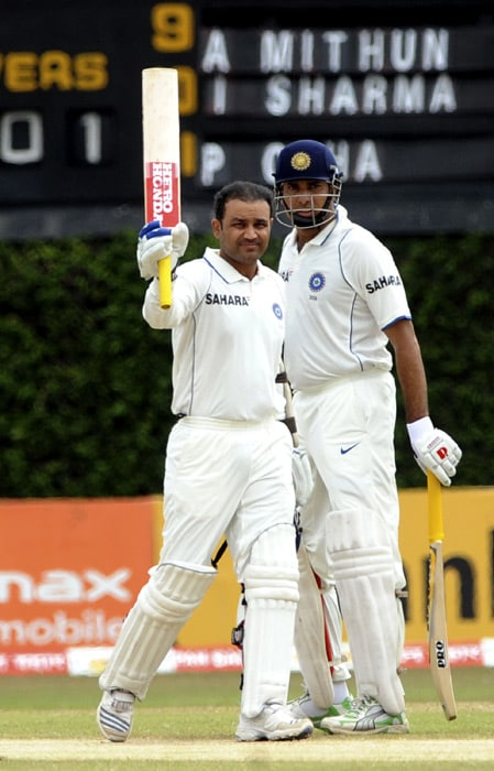 Virender Sehwag (L) is watched by teammate VVS Laxman as he raises his bat and helmet in celebration after scoring a century (100 runs) during the third day of the third Test match between Sri Lanka and India at The P. Sara Oval International Cricket Stadium in Colombo. (AFP Photo)