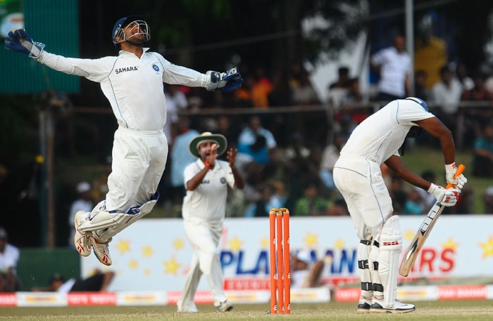 Indian cricket captain and wicketkeeper Mahendra Singh Dhoni (L) leaps into the air as he takes a catch to dismiss Sri Lankan batsman Tharanga Paranawethana (R) during the third day of the third Test match between Sri Lanka and India at The P. Sara Oval International Cricket Stadium. (AFP Photo)