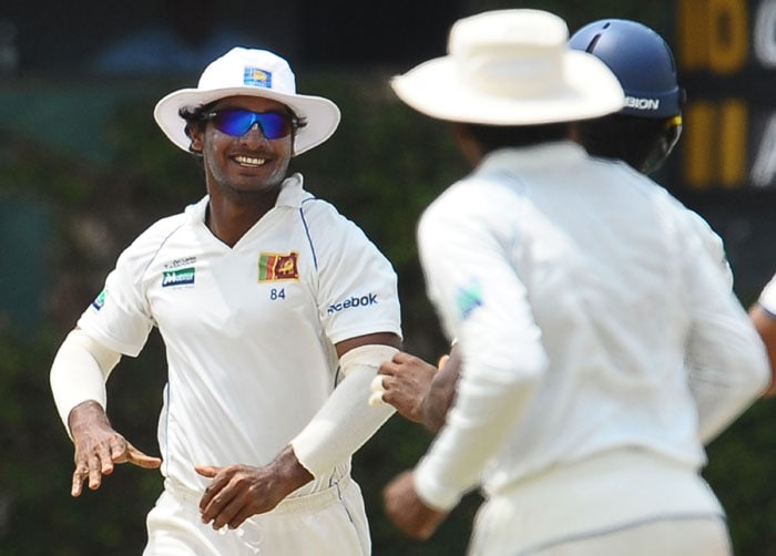 Sri Lankan cricket captain Kumar Sangakkara (L) celebrates after taking a catch to dismiss unseen Indian batsman Suresh Raina during the third day of the third Test match between Sri Lanka and India at The P. Sara Oval International Cricket Stadium in Colombo. (AFP Photo)