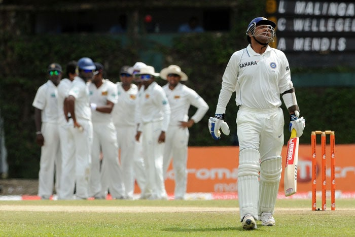 Virender Sehwag (R) walks back to the pavilion after his dismissal during the third day of the third Test match between Sri Lanka and India at The P. Sara Oval International Cricket Stadium in Colombo. (AFP Photo)