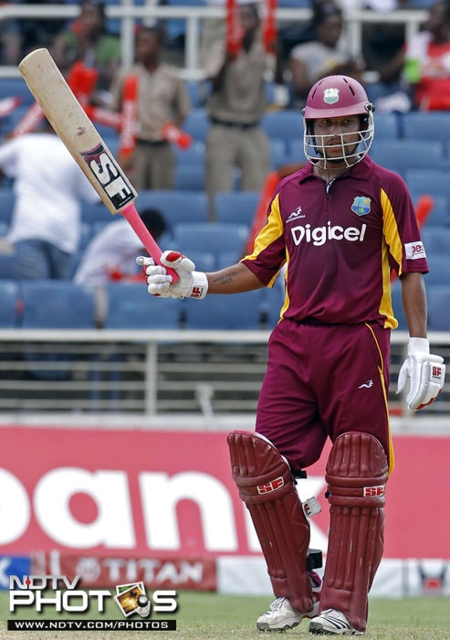 West Indies' Ramnaresh Sarwan raises his bat after scoring 50 runs during the fifth One-Day International against India in Kingston, Jamaica. (AP Photo)