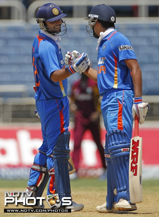 India's Virat Kohli congratulates batting partner Rohit Sharma for hitting a boundary during the fifth One-Day International against West Indies in Kingston, Jamaica. (AP Photo)