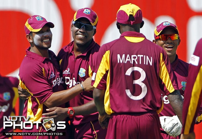 West Indies' Ramnaresh Sarwan is congratulated by teammates after taking the catch to dismiss India's Shikhar Dhawan for 11 runs during their fifth One-Day International in Kingston, Jamaica. (AP Photo)