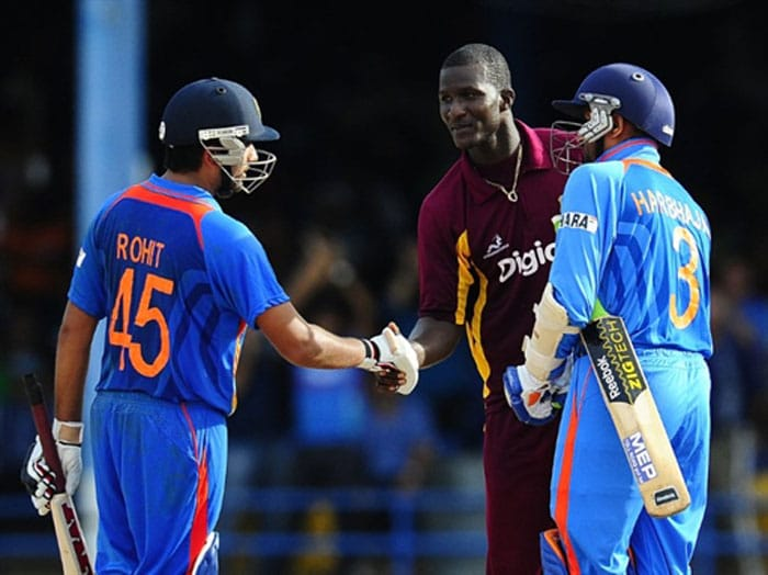 West Indies captain Darren Sammy shakes hands with Indian batsmen Rohit Sharma and Harbhajan Singh after the latter hit India's victory shot during the first ODI between West Indies and India at the Queen's Park Oval in Port of Spain. India scored 217/6 (44.5 overs) in reply to West Indies 214/9 (50 overs). India won by 4 wickets (with 31 balls remaining). (AFP Photo)