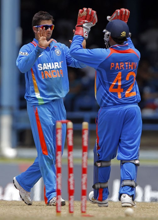 Suresh Raina high fives with the Parthiv Patel after bowling out Marlon Samuels for 55 runs during their first One-Day International in Port of Spain, Trinidad. (AP Photo)
