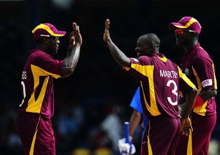 Anthony Martin celebrates with captain Darren Sammy and Kirk Edwards after taking the wicket of Shikhar Dhawan during the first ODI between West Indies and India at the Queen's Park Oval in Port of Spain. (AFP Photo)